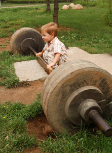 little boy try lift up the barbell in the park
